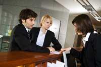 ein Paar diskutiert mit der Frau an der Rezeption