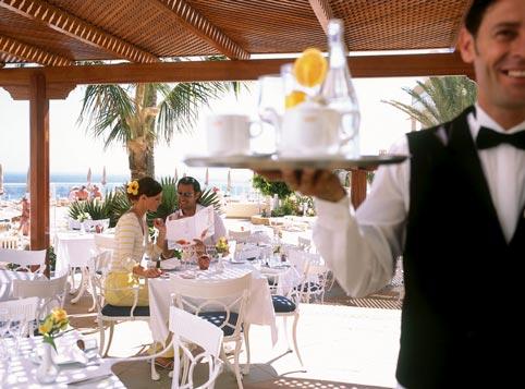 im Vordergrund sieht man einen Kellner bei der Arbeit, im Hintergrund das Kaffeehaus am Strand des Hotels und eine Frau und ein Mann studieren zusammen die Speisekarte