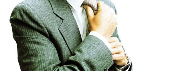 eine Führungskraft im Anzug, beim richten seiner Krawatte