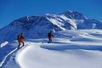 zwei Langläufer sind zu sehen, umgeben von reich an Schnee bedeckten Bergen