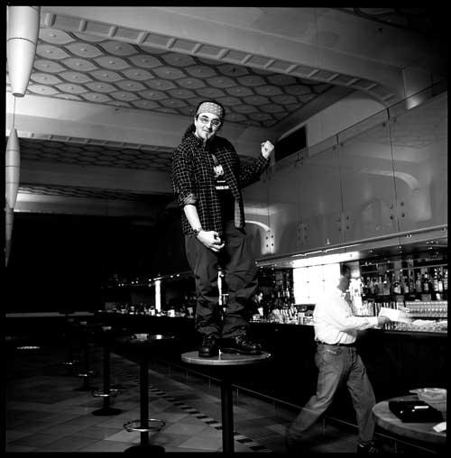 Stefan Marquard steht auf einem Bistrotisch und spielt Luftgitarre