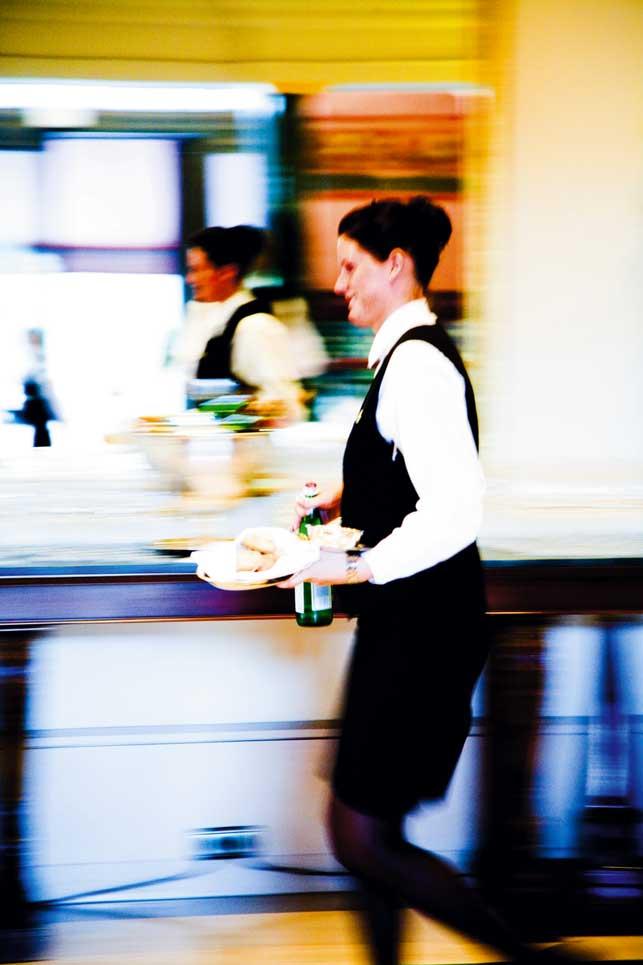 Eine Kellnerin trägt Essen und trinken während sie geht