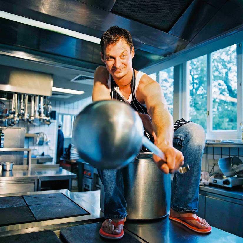 Bernie Rieder sitzt in der Küche auf einem Riesen Kochtopf mit einer Schöpfkelle in der Hand