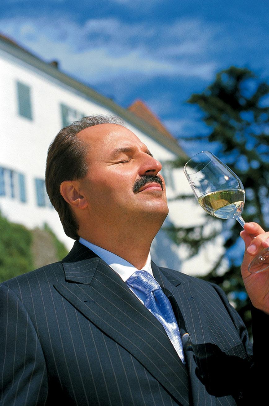 Johann Lafer genießt einen schluck weißwein im sonnenschein