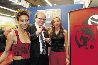 ein Messebesucher posiert mit zwei jungen Damen