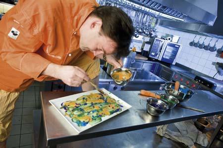 Didi Dorner in orangener Kochjacke verfeinert seine Gerichte