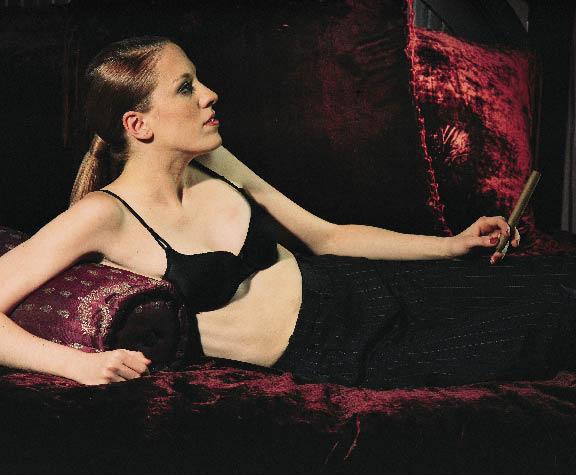 eine Frau liegt in einer schwarzen Bügelfalthose und BH auf einem roten Samtsofa in der Hand eine Zigarre haltend