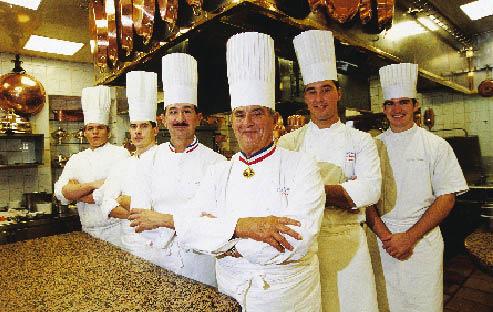 Paul Bocuse und Crew die Arme verschränkt und in der typischen Kochuniform