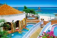 Die Poollandschaft der Hotelanlage direkt am Strand ist zu sehen, auf der kleinen Brücke über dem Pool ist ein Liebespaar zu sehen
