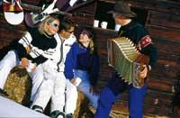 Ein Herr spielt Zierharmonika während drei junge leute fröhlich lauschen und vor einer Skihütte sitzen