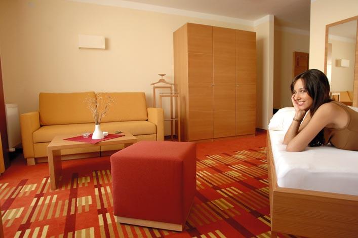 eine Dame liegt auf dem Bett ihres Hotelzimmers mit dem Arm unter ihrem Kopf, des weiteren sieht man einen Kleiderschrank ein kleines Sofa als auch einen Hocker, das Zimmer wird in den Farben Gelb und Rot gehalten