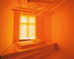 ein Bett vor einem Fenster in einem von orangenem Licht erfüllten Raum