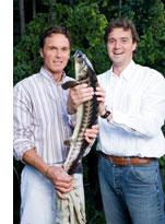 zwei Herren halten stehend zusammen einen Bachsaibling