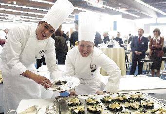 zwei junge köche präsentieren ihre kulinarischen köstlichkeiten