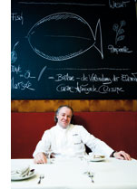 ein Koch im Kochgewand sitzt vor einer grossen gruenen Tafel an der Wand mit einem Fisch aus Kreide darauf gezeichnet