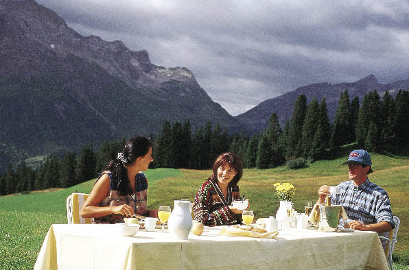 Ein Frühstückstisch auf einer Weide, im Hintergrund Berge und eine Familie die darauf frühstückt