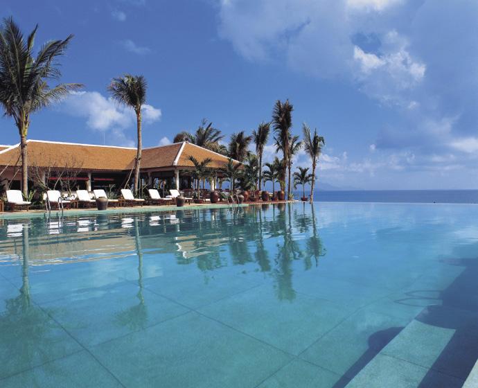 ein endlos langer infinity hotelpool mit wolkenlosem himmel und einzelnen palmen