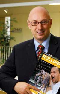 der Herausgeber des Rolling Pin Magazins steht im Anzug da mit einer Ausgabe in der Hand und lächelt in die Kamera