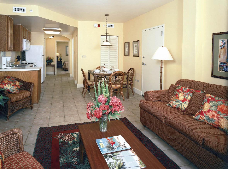 Ein Apartment bestehend aus einer wohnküche und einem essbereich mit einem braunen sofa und einem couchtisch aus holz
