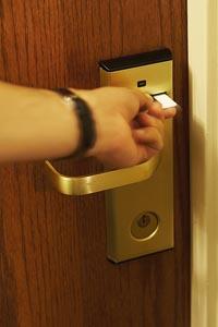 eine Hand öffnet mit der Karte das Hotelzimmer