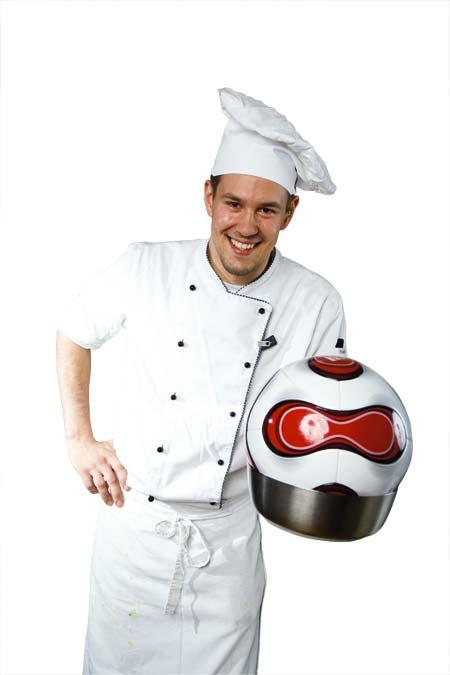 Ein junger Koch hält einen Kochtopf mit einem Fußball darin