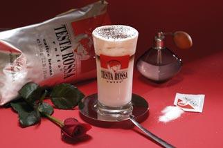 Ein Latte Kaffeeglas, Kaffeebohnen und eine Rose auf einem Tisch
