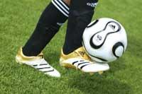 ein Fußball wird von einem Fußballspieler auf dem Rasen gekickt,man sieht nur die Füße bis zu den Knien