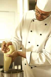 der Koch arbeitet mit einem Spritzbeutel