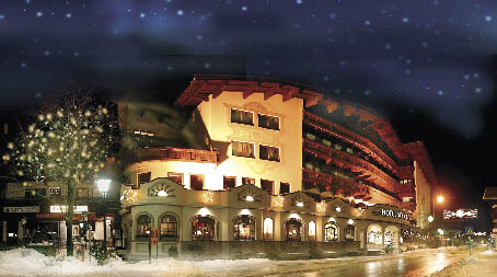 gewölbtes Gebäude in Gelb und beleutet und einem Sternenhimmel im Winter