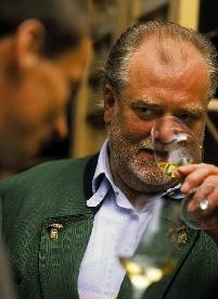 Ein Herr bei der Weinverkostung riecht an seinem Weißweinglas
