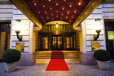 der eingang eines noblen Hotels mit einem langen roten teppich