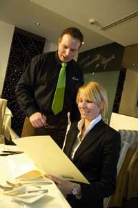 eine Dame im Blazer und ein Herr in Hemd und Krawatte besprechen eventuell die Weinkarte