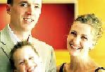 eine Junge Familie, bestehend aus mutter vater und kind lächeln in die kamera