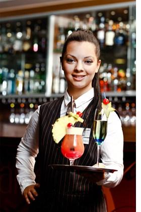 eine Kellnerin mit einem Cocktail auf dem Tablett