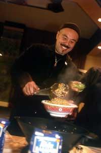 ein Koch füllt lächelnd eine Schüssel mit Essen an
