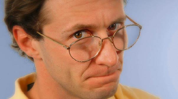 ein Mann mit einer Lesebrille sieht skeptisch in die Kamera