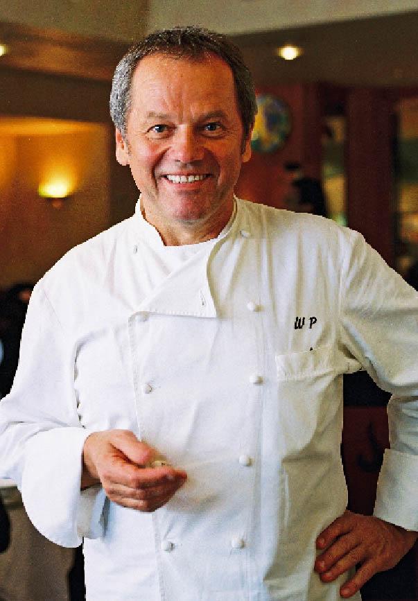 Wolfgang Puck in weißer Kochjacke, auf der Brust seine Initalien