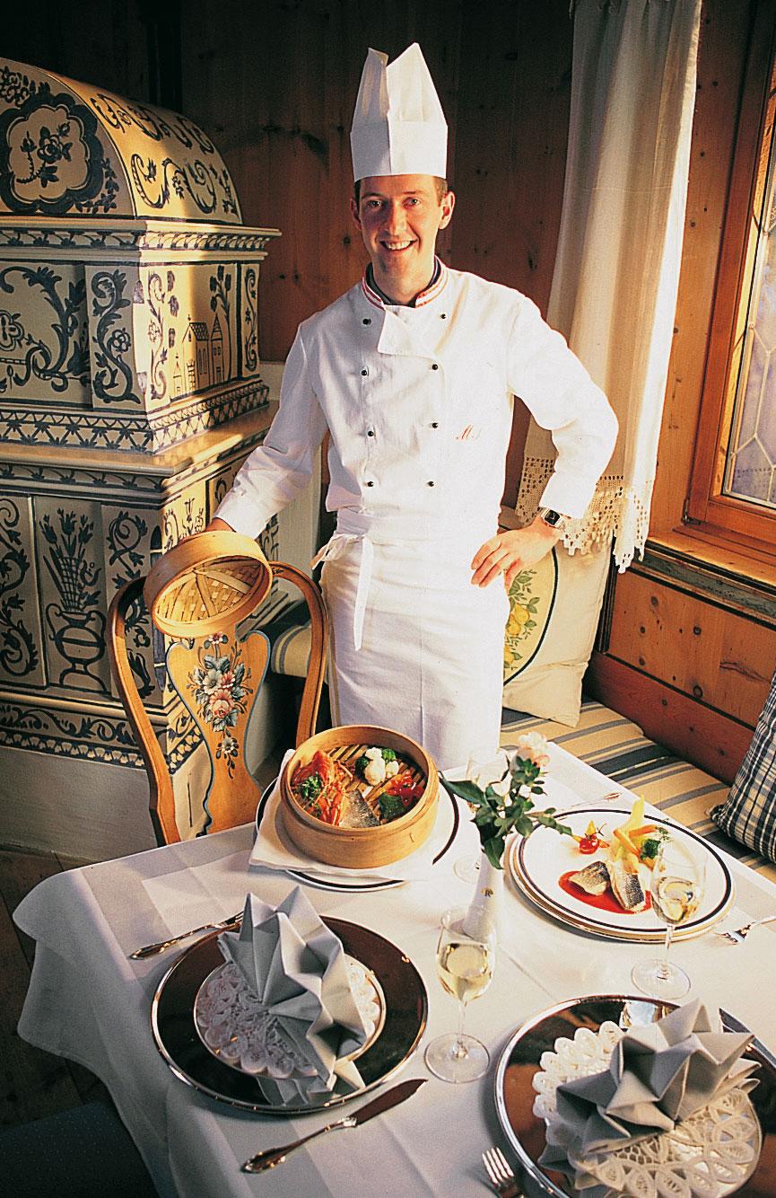 martin sieberer in Kochbekleidung vor einem reich gedeckten tisch
