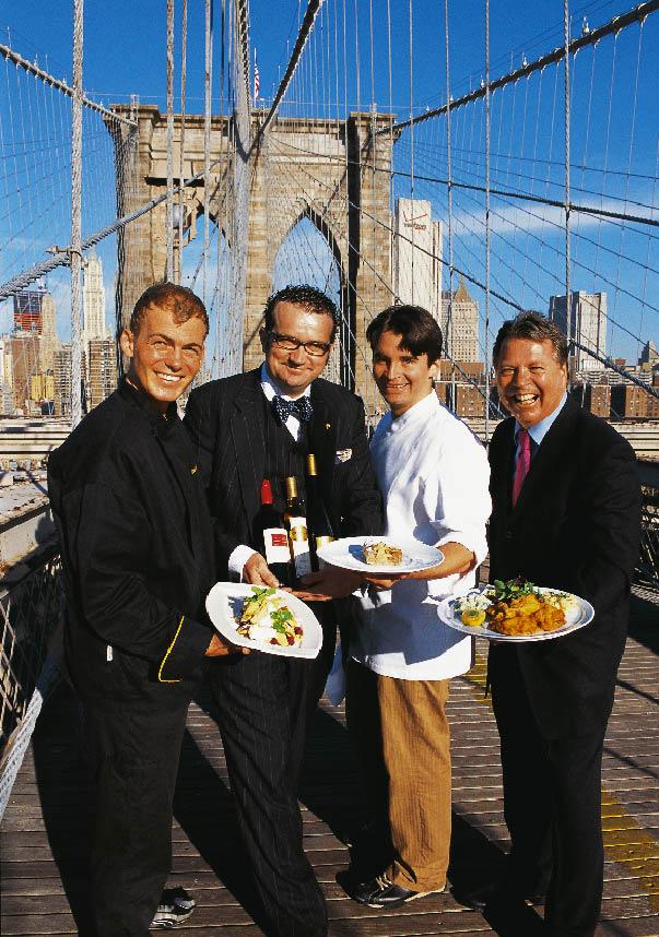 vier Herren stehen auf der Brooklyn Bridge in New York mit Tellern gefüllt mit kulinarischen Köstlichkeiten