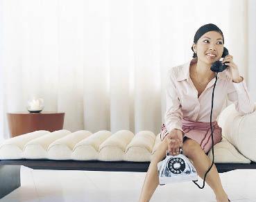 eine junge Frau sitzt auf einer gepolsterten Sitzbank und telefoniert mit einem Festnetztelefon