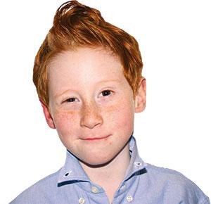 ein rothaariger kleiner Junge in einem blauen Hemd