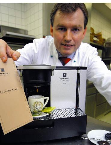 Ein Mann steht hinter einer Espressomaschine während diese Kaffee herunter lässt