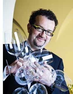 ein Herr mit mindestens einem Dutzend leerer Weingläser in seinen Armen