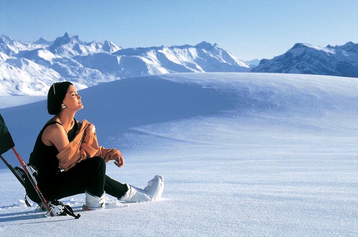 Eine Frau sitzt auf einem von Schnee bedecktem Berg und genießt die Sonnenstrahlen