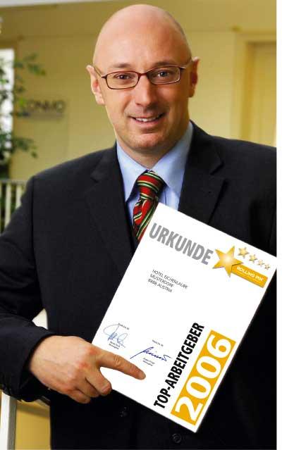 Herr Jürgen Pichler steht im Anzug und hält die Urkunde des Top Arbeitgebers 2006 vor der Brust