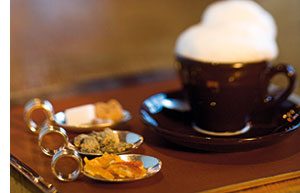 eine Tasse Kaffee mit Milchschaum und drei Loeffel mit Zucker und Sueskram