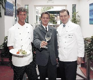 Drei Herren stehen in einem Flur, einer hält einen Teller gefüllt mit einer köstlichen Kreation und der zweite hält ein weinglas