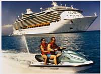 ein Paar fährt Jet-Ski während im Hintergrund ein Kreuzfahrtschiff zu sehen ist