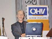 Ein Herr sitzt vor seinem Laptop vor dem ÖHV Banner