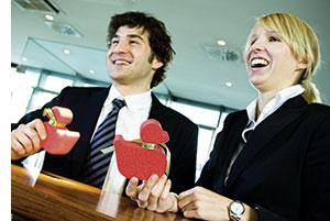 eine Frau und ein Mann stehen an einem Tresen gelehnt, mit einer roten Spielente in der Hand, beide sehen froehlich lachend aus